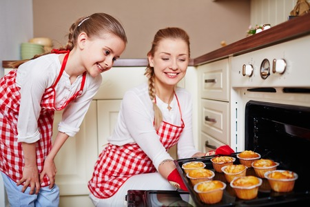 Adorable girl and her mother taking out muffins from oven Stock Photo