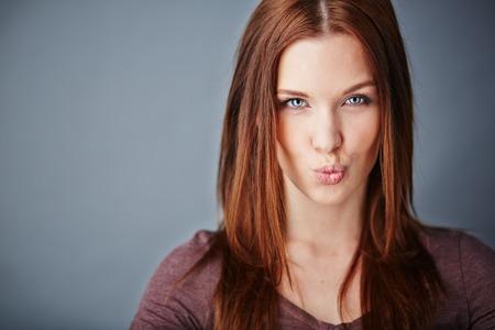 hot love: Young woman expressing air kiss while looking at camera Stock Photo
