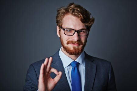 okay: Confident businessman in eyeglasses showing okay sign