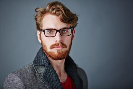 スマート普段着とカメラ目線の眼鏡で髭の男