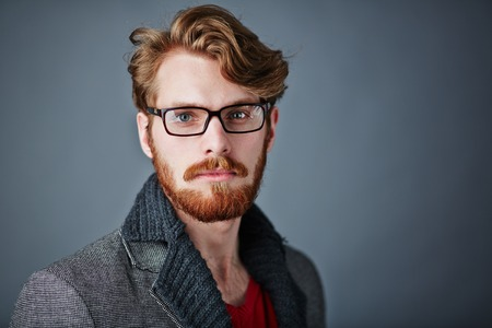 hombre con barba: Hombre barbudo en ropa casual elegante y gafas mirando a la cámara