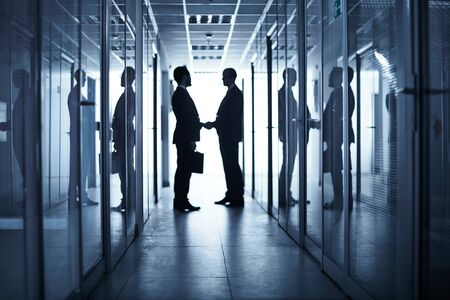 partner: Silhouettes of two business partners handshaking in corridor of office building after negotiations Stock Photo