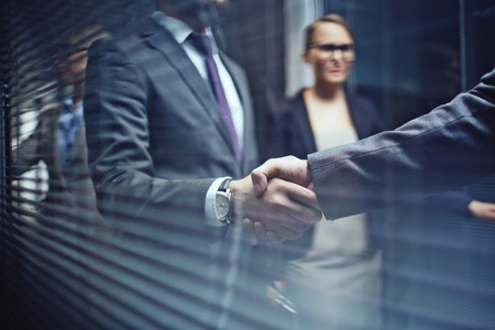 negotiation business: Close-up of businessmen handshaking on background of woman