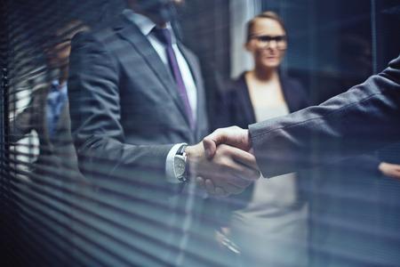 negociacion: Primer plano de los hombres de negocios apret�n de manos en el fondo de la mujer
