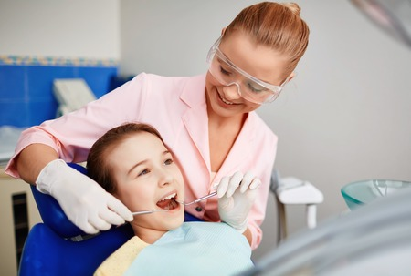 Female dentist checking up teeth of cute child Stock Photo