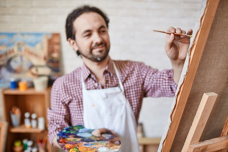 Male artist painting on canvas