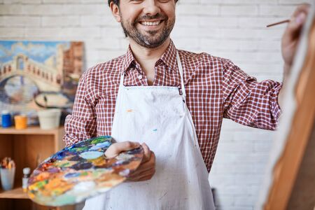 mixed colors: Happy artist holding palette with mixed colors while painting Stock Photo