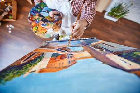 Male artist painting street of Venice on canvas photo