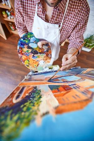 男性アーティストのキャンバスに油絵具で絵画