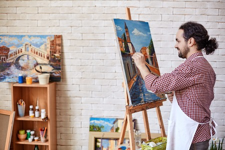 artistas: Pintor hermoso que trabaja en su estudio Foto de archivo