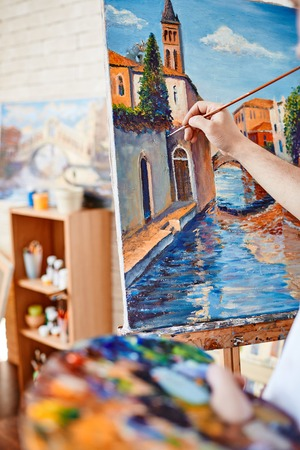 Hand of artist painting street of Venice on canvas Stock Photo