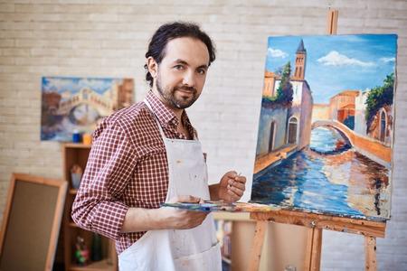 hombre pintando: Artista joven que mira la cámara en el fondo de su pintura