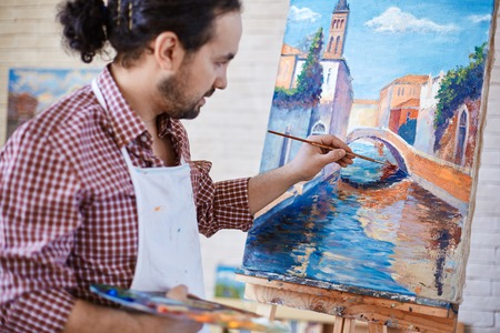 modern painting: Young artist painting Italian landmark in studio