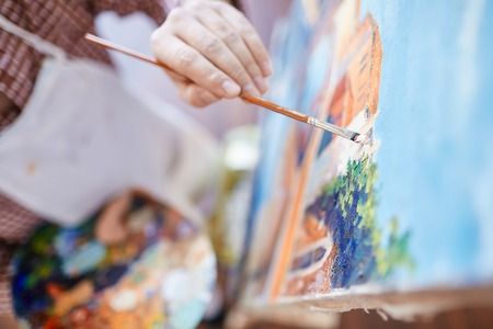 Hand of artist with paintbrush painting on canvas photo