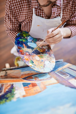 Man with paintbrush mixing water-colors photo