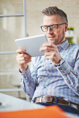 restful: Restful businessman with touchpad sitting in office