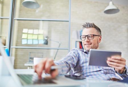empleados trabajando: Hombre de negocios maduro adictos a los gadgets que tienen descanso