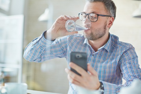 Mature businessman in eyeglasses drinking water while using smartphone in office
