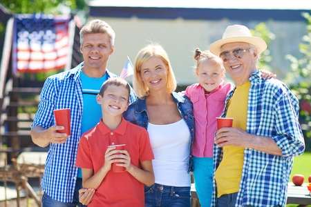 grandkids: Happy senior man, young couple and their two children looking at camera Stock Photo