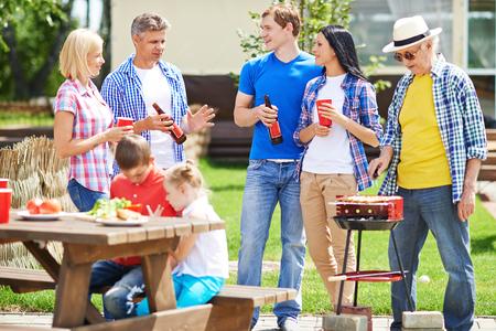 family picnic: Dos pares de descanso hablando al aire libre con el hombre mayor freír salchichas en la parrilla cerca