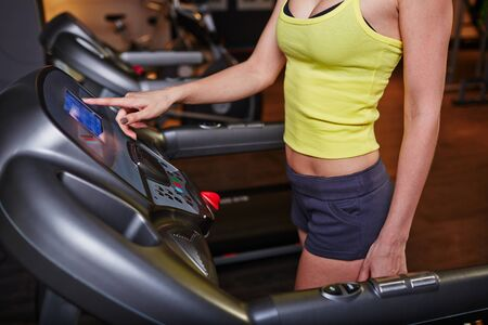 activewear: Fit girl in activewear training on sportive equipment