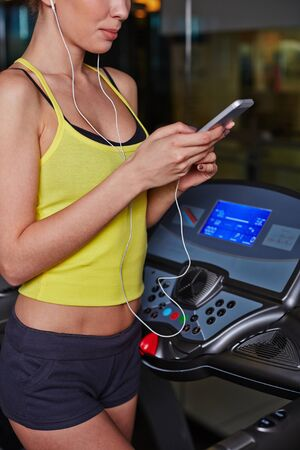 activewear: Fit girl in activewear listening to music in ipad in gym
