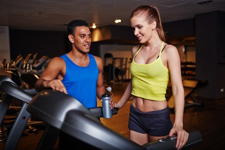 activewear: Fit girl and guy in activewear spending time in gym