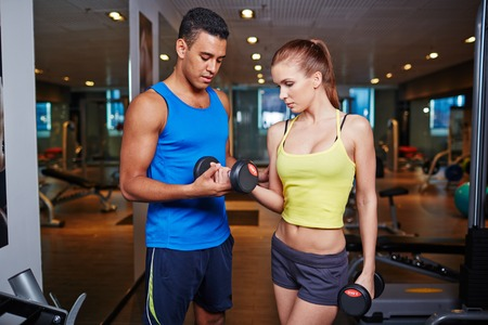 activewear: Fit girl in activewear learning to exercise with barbells Stock Photo