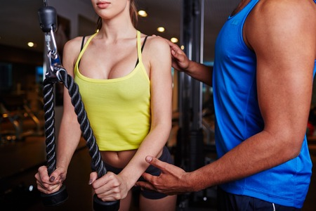activewear: Young woman exercising on sports facilities in gym with help of trainer