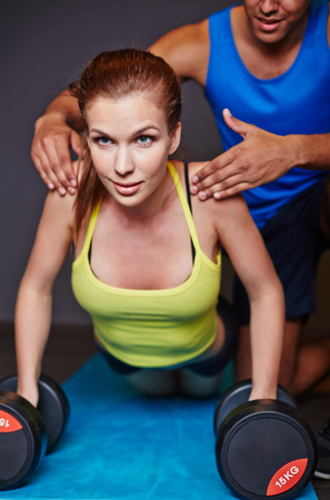 activewear: Young woman practicing weightlifting in gym with help of trainer