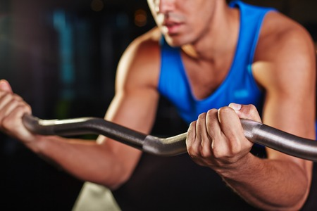 levantar peso: hombre joven, levantamiento de peso durante el entrenamiento Foto de archivo