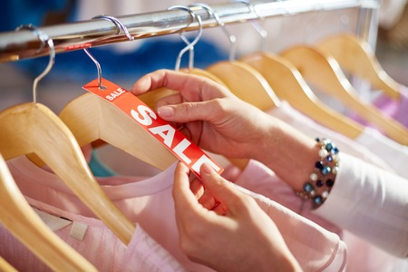 shopaholism: Female hand holding sale label on one of hangers with collection of clothes Stock Photo
