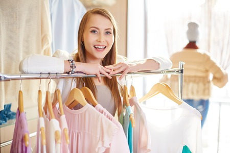 shopaholism: Attractive woman looking at camera in clothing department