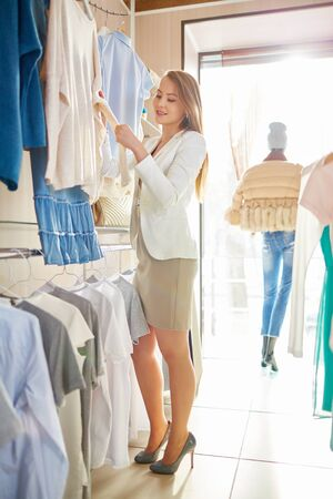 shopaholism: Elegant girl looking through new collection of clothes in boutique