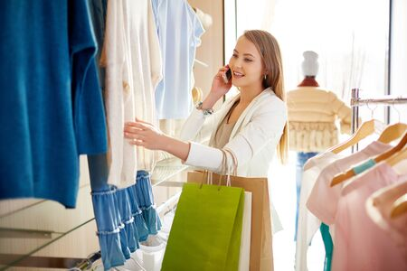 shopaholism: Modern woman speaking on the phone while looking through new collection of clothes in boutique Stock Photo