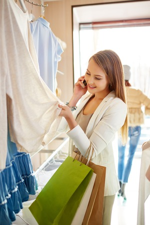 shopaholism: Young woman speaking on the phone while choosing new pullover in boutique Stock Photo