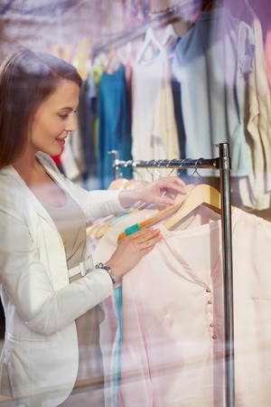 shopaholism: Female choosing new blouse in boutique
