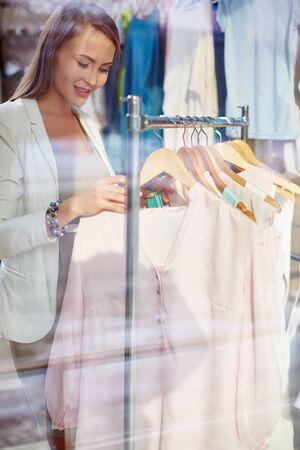 shopper: Young shopper looking through new clothes Stock Photo