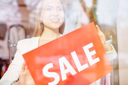 shop assistant: Beautiful shop assistant announcing sale season