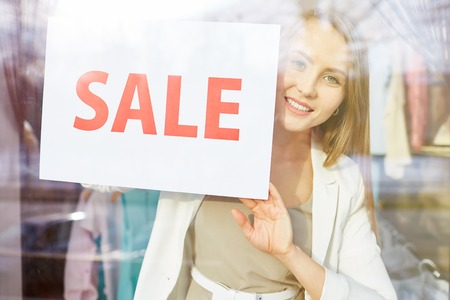 shopaholism: Beautiful young woman with sale announcement looking at camera from shop window