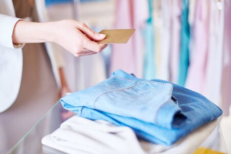 shopaholism: Shopper giving plastic card to assistant over chosen clothes