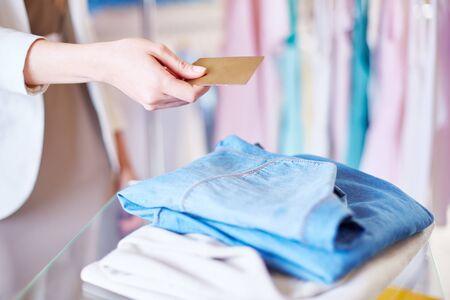 shopaholism: Shopper giving plastic card to assistant over chosen clothes