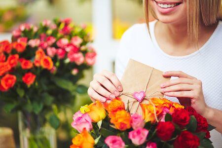 mazzo di fiori: Sorridente fiorista mettendo messaggio per la ricevente in bouquet di rose Archivio Fotografico