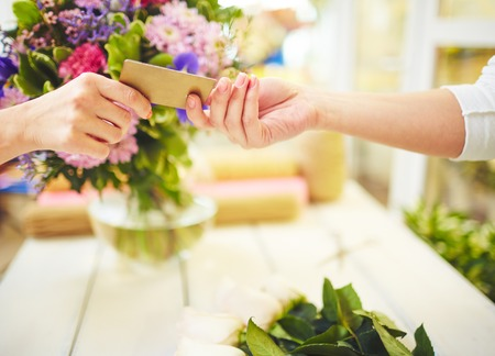 flowers close up: Female florist taking credit card for payment Stock Photo