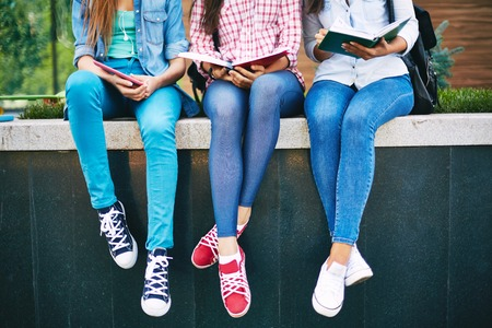 Modern teen girls reading outside Stock Photo