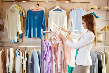 Elegant girl choosing blouse from new collection of clothes in boutique