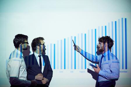 explaining: Confident businessman explaining his colleagues chart of financial progress Stock Photo