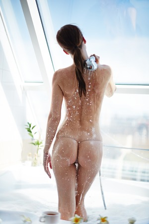 Back view of bare female taking shower