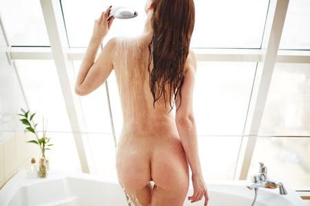 Vista trasera de la mujer que toma la ducha joven desnudo