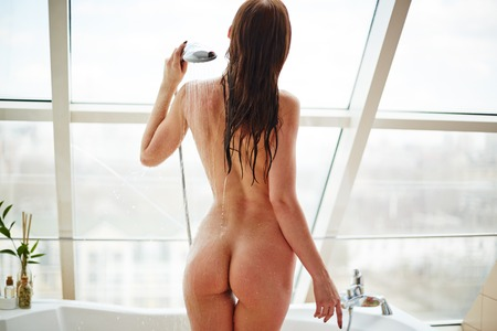 desnudo de mujer: Volver la vista de mujer atractiva salpicar a sí misma de la ducha